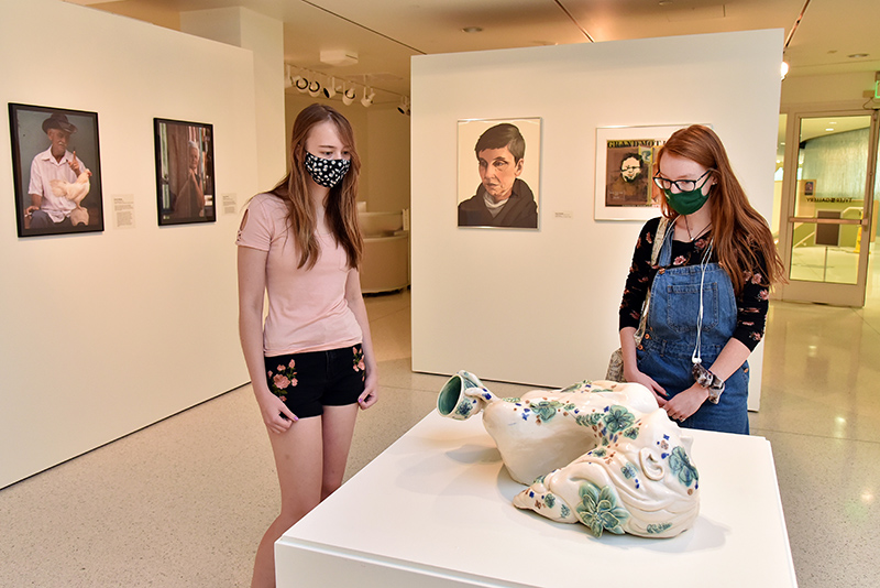 """Looking at a ceramic sculpture titled """"Holding Tight, Letting Go,"""" which is a 2011 Presidential Purchase Award by artist and former SUNY Oswego student Caroline Hayward, are Ellen Weber (left), a junior graphic design major and art gallery attendant, and Megan Campbell, a senior theatre major"""