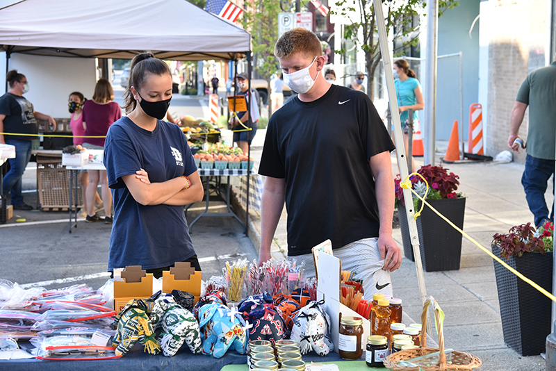 Audrey Meany, a December 2019 health education graduate, and John Kilkenny, an MBA/accounting graduate student, check out the Oswego Farmers' Market along West First Street on Sept. 3, which was College Night at the popular Thursday event.