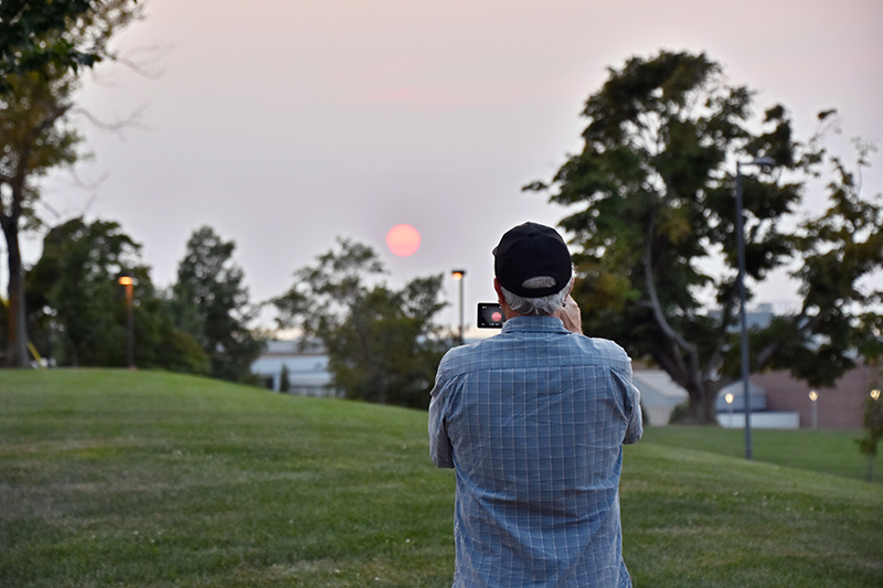 An area resident and 1974 Oswego alumnus captures the sunset with camera and tripod Sept. 16 as it sets over Marano Campus Center.