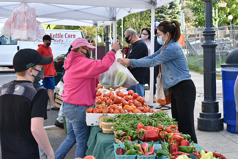 Renqian Yang, an art department faculty member who teaches ceramics, buys some locally-grown fresh produce Sept, 17 from Ingersoll Farms from Fulton at the Oswego Farmer's market on West First Street.