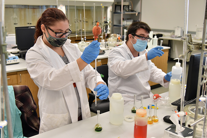Working with instrumentation to analyze acidic ph levels with indicator solutions are Anna Makara, a senior chemistry major with concentration in environmental chemistry, and Michael Kirsch, a senior biochemistry major.