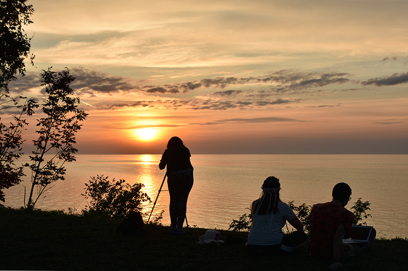 Students Payton Beauregard, Caysie Schrader and Michael Cinelli -- shown in an earlier photo setting up for the sunset -- get their majestic payoff over Lake Ontario.