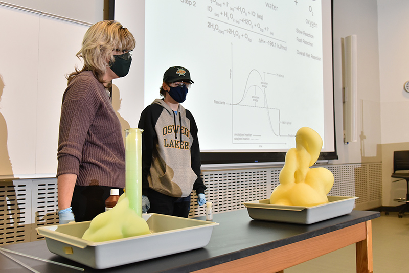 """Timothy Moorhouse, a freshman chemistry major in Kristin Gublo's first-year seminar class (CHE 110F), demonstrates the creation of """"Elephant Toothpaste."""" Once the catalyst is added to the simple ingredients, the volume greatly expands to overflow the container."""
