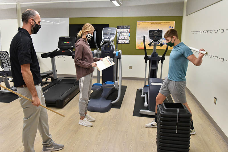 """Griffin Biviano (right), a freshman health and wellness major, and Peyton Daeffler, a sophomore wellness management and nutrition major, work in the """"Intro to Personal Training"""" class taught by Brian Wallace (left) in the Wellness Lab in the basement of Wilber Hall."""
