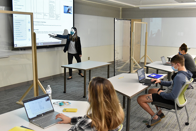 Elizabeth Keida teaches a wellness class -- complete with masks and facility features reflecting current health protocols -- in recently renovated room B5 of Wilber Hall.