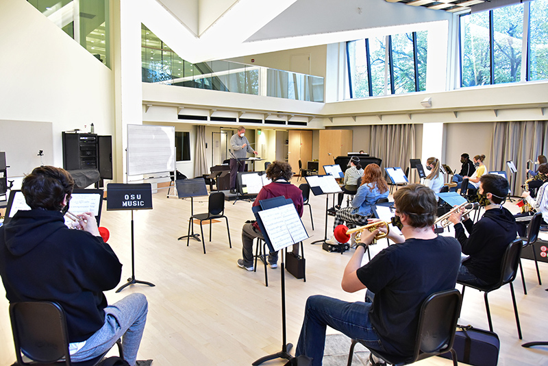 The college's Wind Ensemble conducts a class and rehearsal under the direction of music faculty member and chair Trevor Jorgensen. The new normal for the group includes special masks and windscreens, as well as breaks to clear out Room 11 in Tyler Hall.