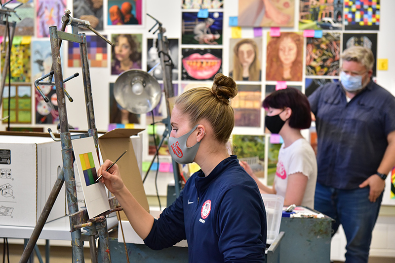 Malia Minckler (foreground), a senior art/illustration major, works on a painting during a painting class taught by Christopher McEvoy. In the background, Kate Miller, a sophomore art/graphic design major, gets some feedback from McEvoy.