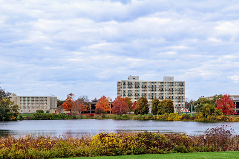 Colors on trees and an outdoor tent ring Glimmerglass Lagoon looking toward West Campus in this late October image. (Photo by Nsikak Ekong)