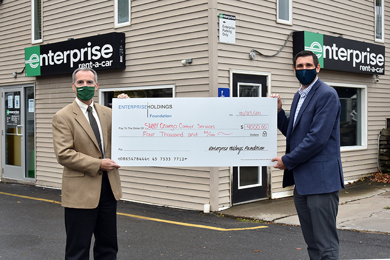 Enterprise Holdings Foundation presents a check for $4,000 to SUNY Oswego of Office Career Services. Presenting the check is Jody Giarrusso (right), talent acquisition specialist with Enterprise Human Resources. Accepting is Gary Morris (at left), director of SUNY Oswego Career Services.