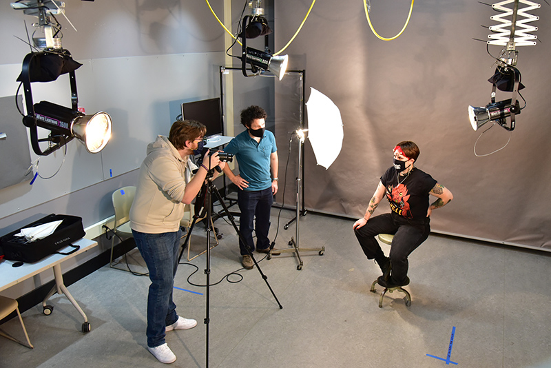 """Patrick Higgins, a junior graphic design major, sets up a studio portrait in Tyler Hall's art photography studio of Kayli Clubine, a senior studio art major, during a """"Digital Photography"""" class with art faculty member Peter Cardone (center)."""