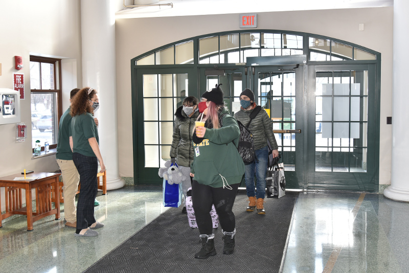 Elizabeth Maldonado enters the Johnson Hall main entrance on Jan. 24 with some family members helping her with her belongings.