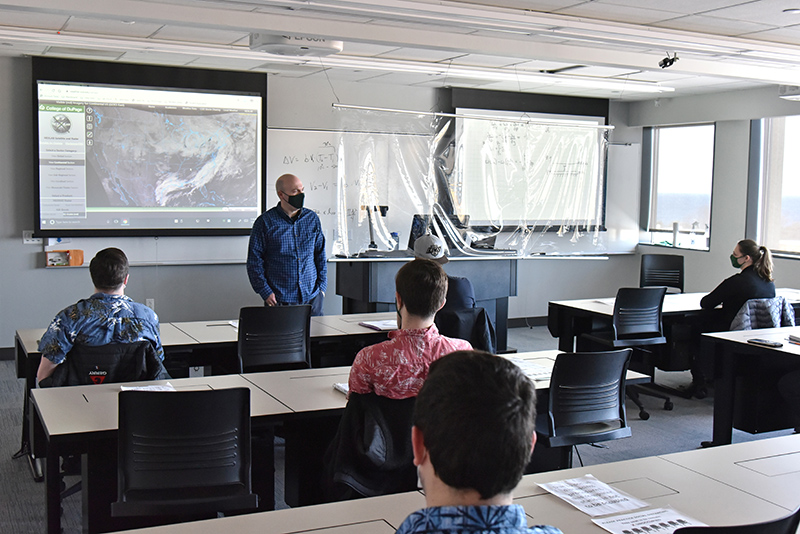 Atmospheric and geological sciences faculty member Scott Steiger teaches a meteorology class to students in the Shineman Center on Feb. 5, also the date of National Weather Person's Day
