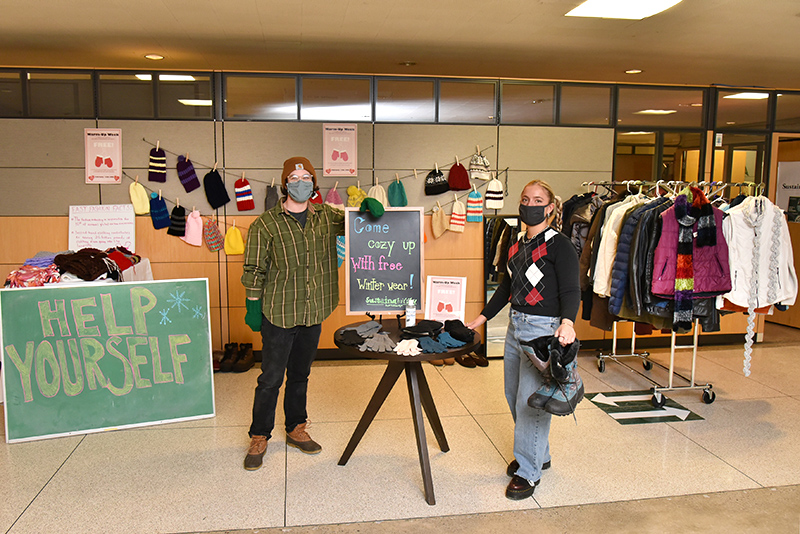 Sustainability Office interns Jonathan Mills, a graduate student in art, and Sarah Smelko, a senior global studies major, show off some of the free winter clothing offered in Hewitt during an ongoing free winter Warm-up Week clothing and gear giveaway