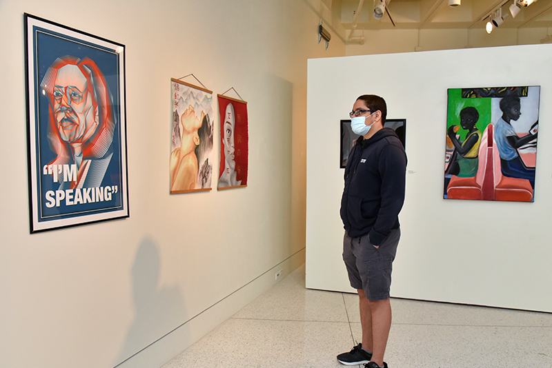 Emilio Jimenez, a freshman graphic design major and a Tyler Art Gallery attendant, looks at work on exhibit in the 58th annual Juried Student Art Exhibition