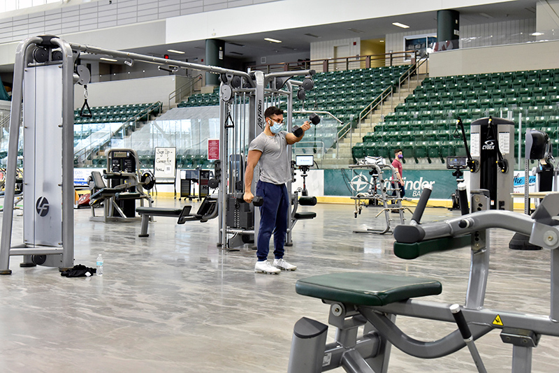 Erik Vergara, a senior finance major, works with some of the exercise equipment in Marano Campus Center Arena that was temporarily moved from Cooper in order to proved greater, more socially distanced space