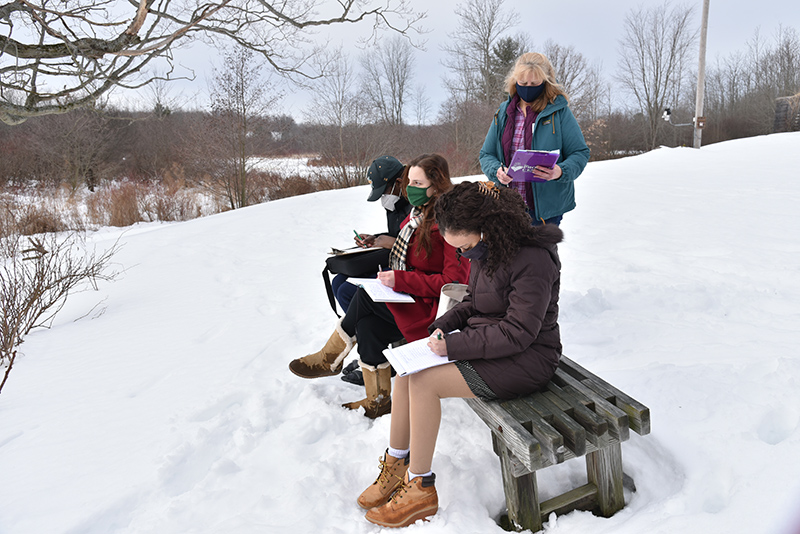 """The Nature Writing workshop, led by Rice Creek Field Station naturalist Linda Knowles (standing), featured student writers Heaven Santiago (foreground), Rachel Blake and Ryan Ravenell enjoying some of their """"natural"""" creativity during Wellness Day on Feb. 24."""