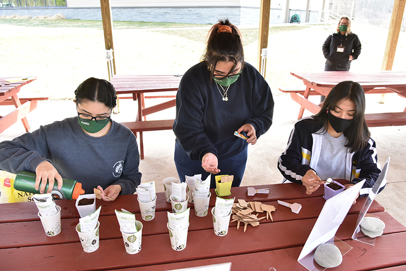 Pictured planting seeds of edible flowers and spices including chives, marigold and basil are sophomores, from left: Arianna Padilla, a psychology and wellness management dual major, Alexa Caban, a cinema and screen studies major, and Maria Salinas, a biological science major.
