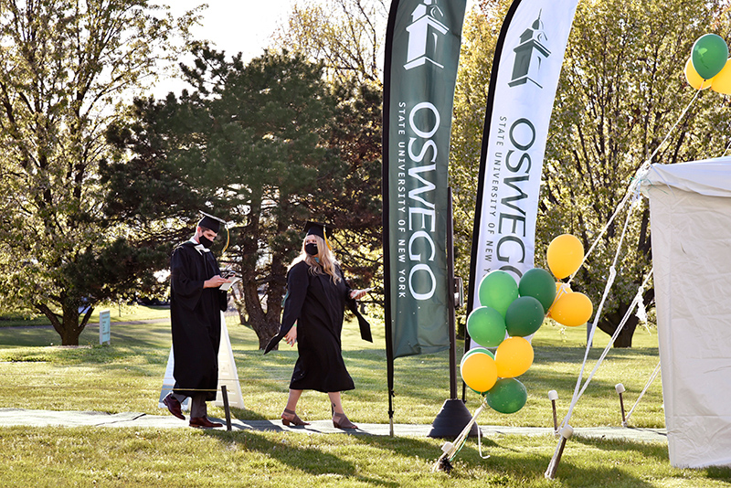 Students earning graduate degrees walk May 14 to the check-in tent on the north lawn of Marano Campus Center before their ceremony in the building's convocation hall and arena.