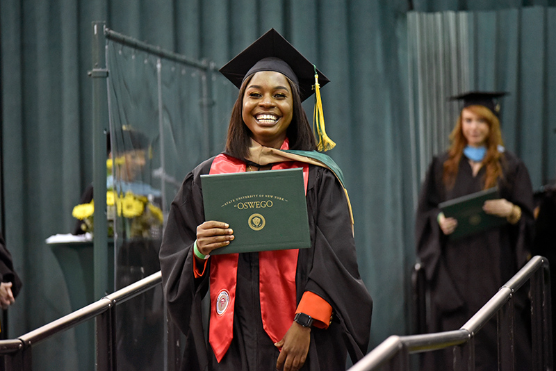 Blessed Sampa, who earned her MBA and bachelor's degrees, flashes a joyful smile displaying her diploma May 14 as she walks across the commencement platform in Marano Campus Center.