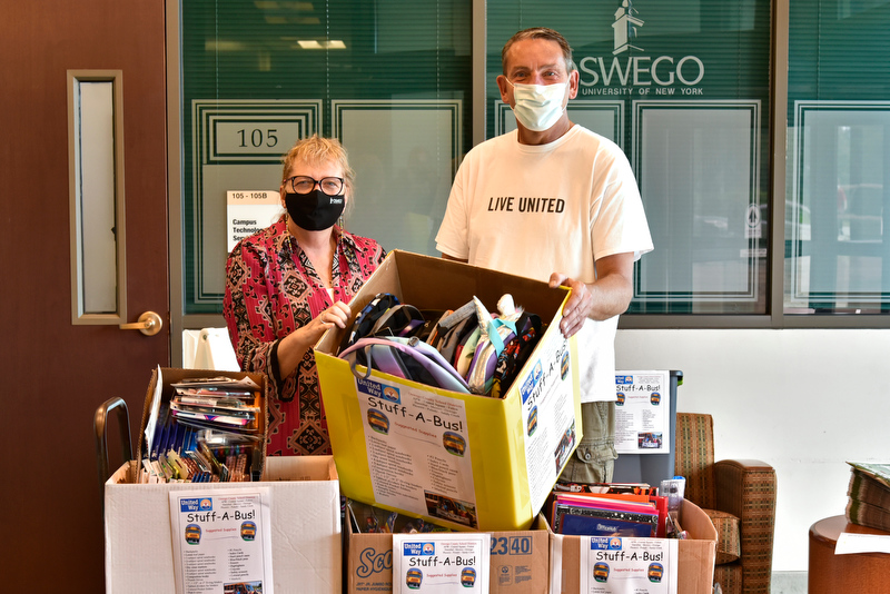 Cathy Johnston, assistant to the provost at and member of the State Employees Federated Appeal Planning Committee, and Patrick DeWine from the United Way of Greater Oswego County, display some of the school supplies collected during the SEFA's annual Stuff A Bus drive which provides supplies to support school children around Oswego County.