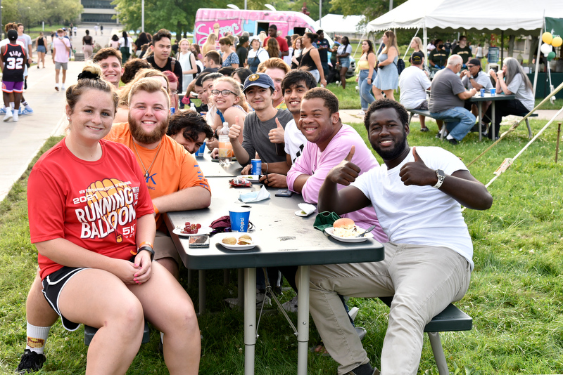 Yahya Ndiaye (right), a Laker Leader captain and double major in electrical and computer engineering and in French, gives a thumbs-up with friends at the Welcome Picnic Aug. 20.