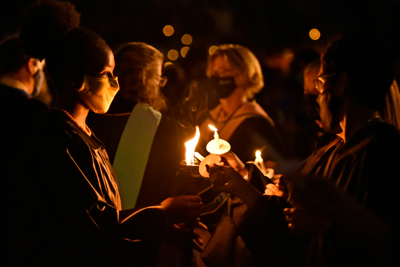 Senior Takayla Beckon, Student Association president and torchbearer, lights the candles of students and faculty at Welcoming Torchlight.