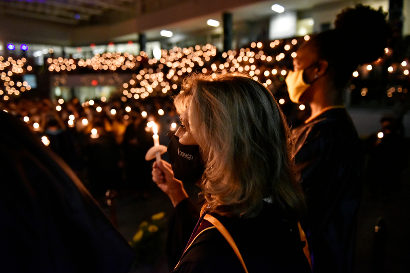 College President Deborah F. Stanley (left) and torchbearer Takayla Beckon, Student Association president, lift their candles at the conclusion of the 32nd annual Welcoming Torchlight Ceremony on Friday, Aug. 20. The ceremony is a traditional introduction to the academic year.