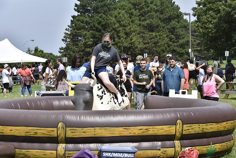 Niamh Walsh, a sophomore majoring in illustration, rides the mechanical rodeo bull during Lakerfest. Throngs of students came out Sept. 28 to enjoy the fun and food at the west campus residence halls location, which featured a variety of food, games, bounce houses, a high flying zipline and more.