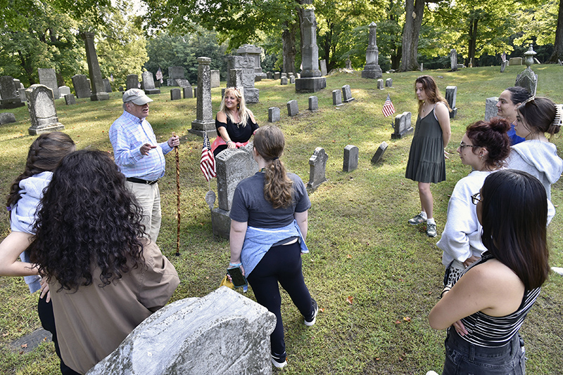 Theatre faculty member Jonel Langenfeld's storytelling class visited the Oswego Town Rural Cemetery where they will hold a live public performance featuring notable people of the past. On hand was Oswego Town Historian George DeMass, who also is a 1966 Oswego alumnus.