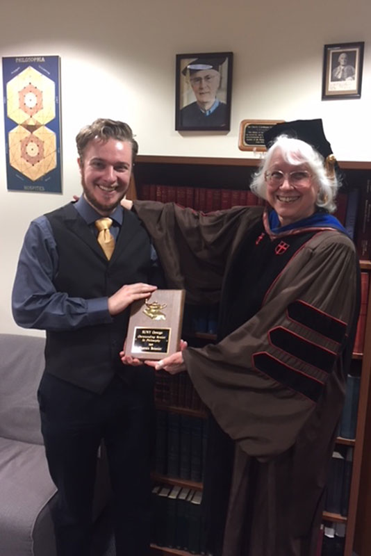 Philosophy honoree Phoenix Boisnier and department chair Jean Chambers display Boisnier's award