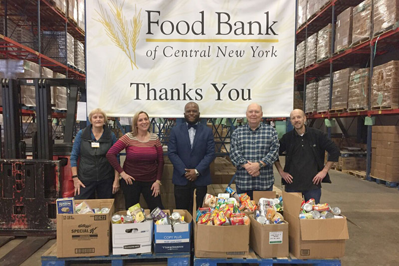 Isiah Brown with Food Bank of CNY representatives with campus donations