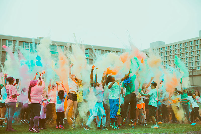 Students throwing colorful powder on runners