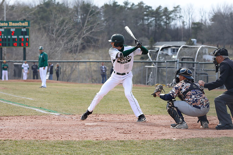 Oswego baseball player Michael Dellicari bats, striding into a pitch