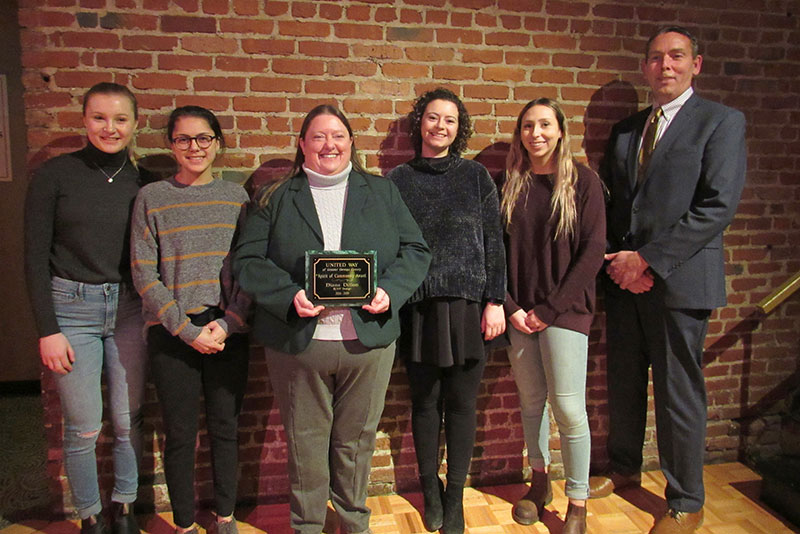 Women's hockey coach Diane Dillon collects community service award with four of her players