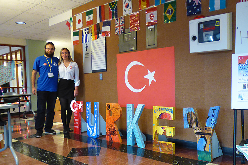 Turkish students Emir Tortopoglu and Fem Koymen stand in Hart Hall lobby next to artwork connecting to their home country