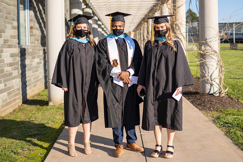 Three master's candidates arrive for the Friday, May 14, ceremony for graduate students and others earning their advanced degrees and certificates.