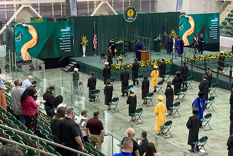 Participants and attendees stand during Commencement ceremonies to sing the college's alma mater.