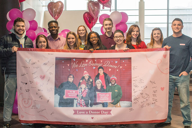 Students pose with banner at Love a Donor Day event