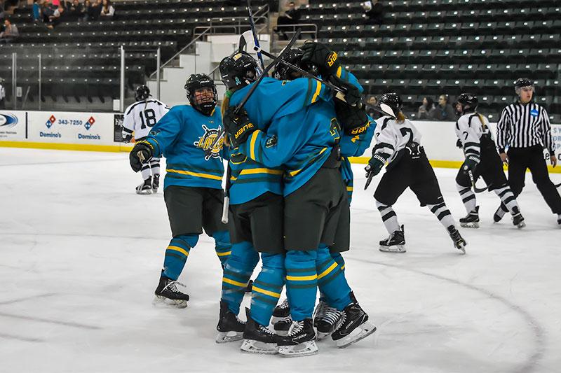 Laker women's hockey players celebrate goal in a big hug