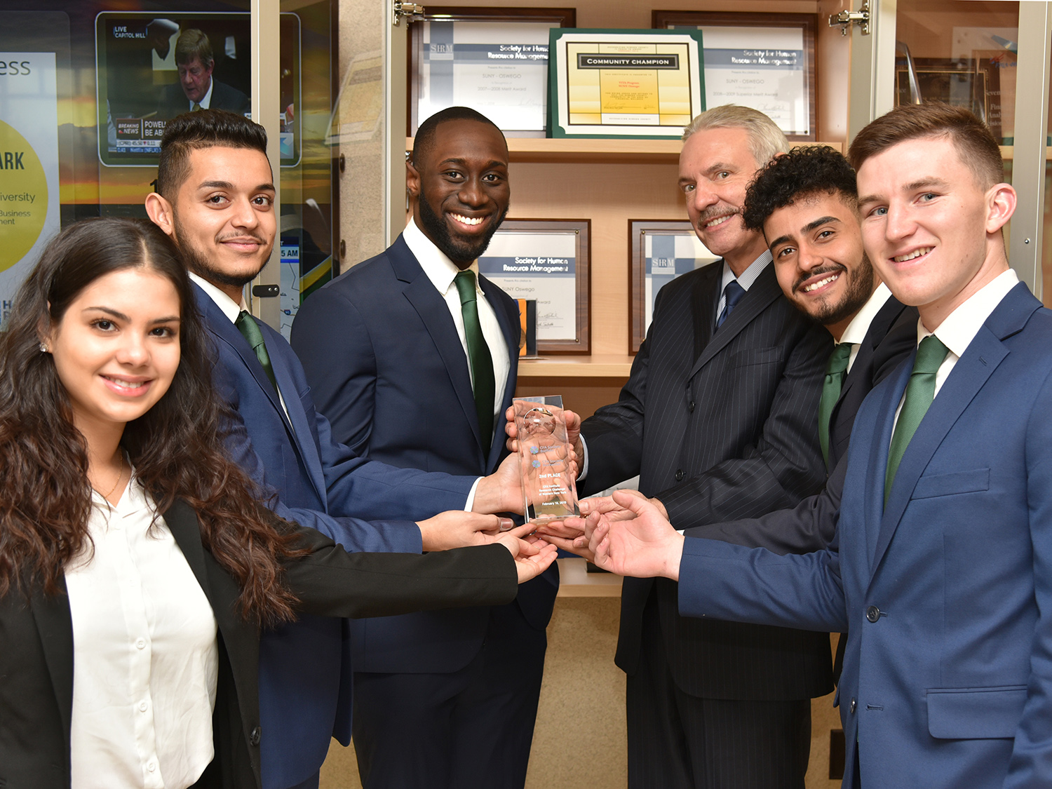Students who placed in CFA challenge present Dean of Business Richard Skolnik with trophy