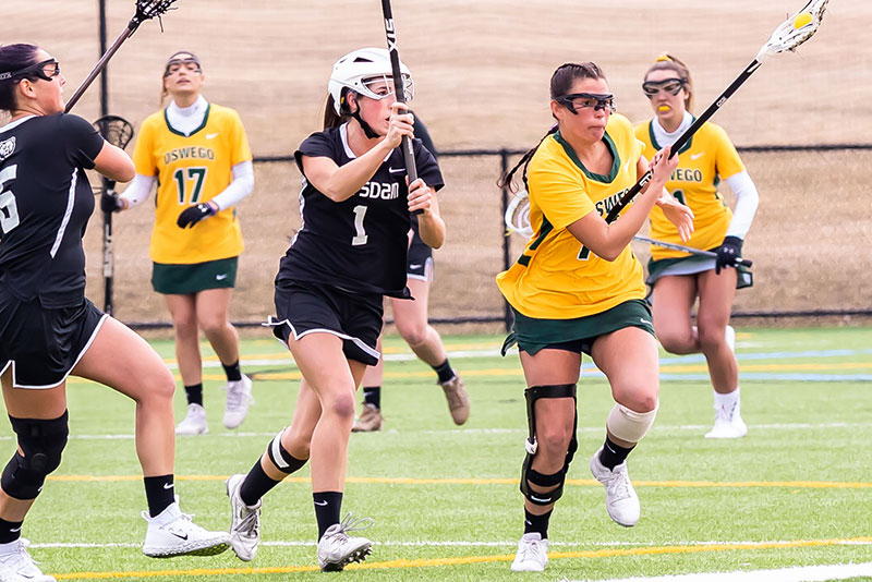 Women's lacrosse player Teresa Shattuck of Oswego runs past Potsdam defenders as she cradles the ball