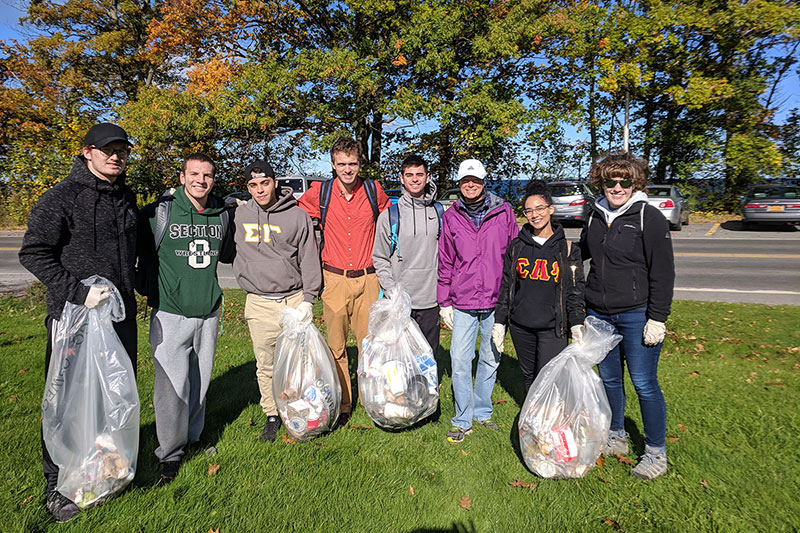 Students showing bags of waste they picked up during a lakeshore cleanup