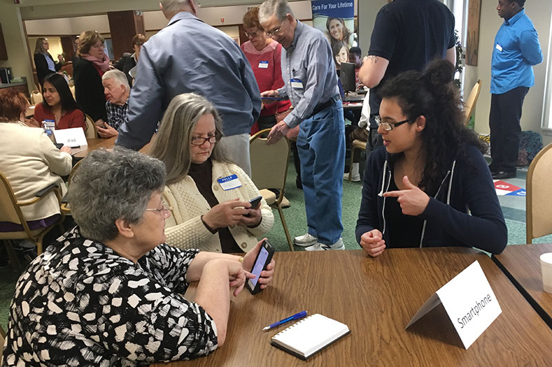 Students help senior citizens with questions about technology