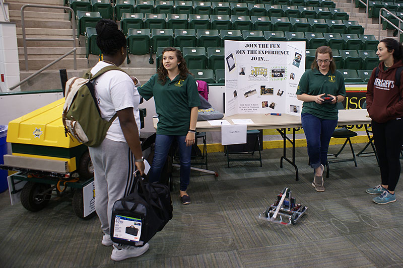 Team Mini members with mini-Zamboni and robot speak to students