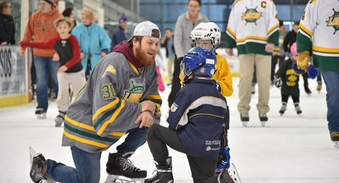 Cedric Hansen of the Laker men's hockey team talks with young skaters