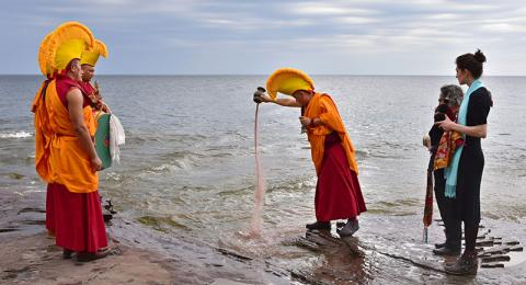 "A Drepung Loseling monk pours colored sand into Lake Ontario as part of the closing ceremony of ""The Mystical Arts of Tibet"""