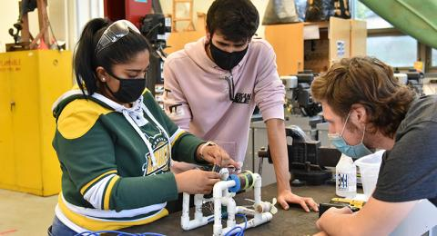 Working on a class assignment project that incorporates floating vehicle buoyancy, hydraulics, pumps and battery powered motors are (from left) junior technology education majors Shafia Ibrahim, Hunter Sabella and Ryan Parrish.