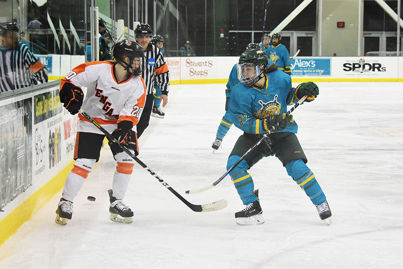 Oswego women's hockey players move the puck in advance of a goal
