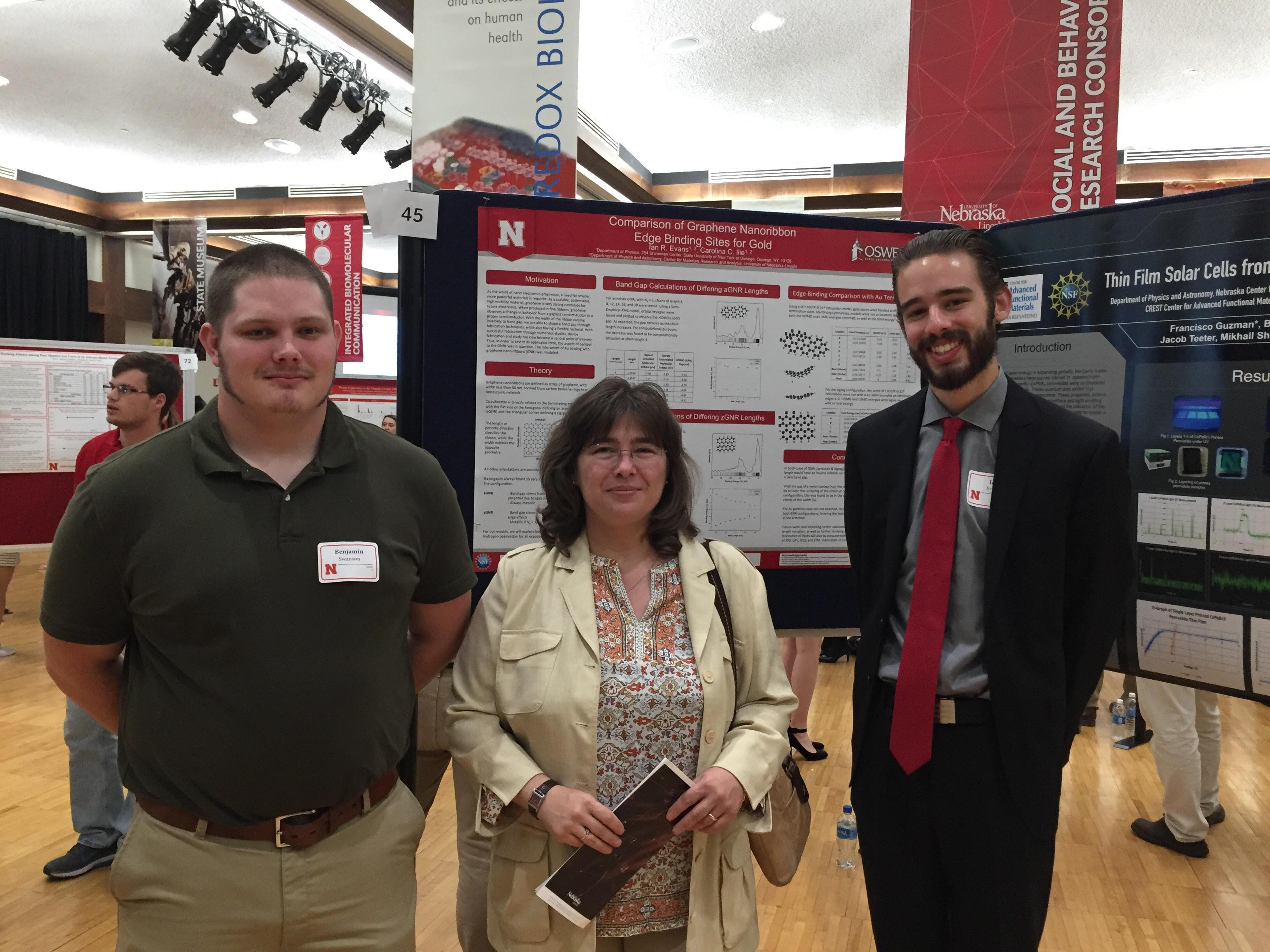 Professor Carolina Ilie with two students presenting research poster