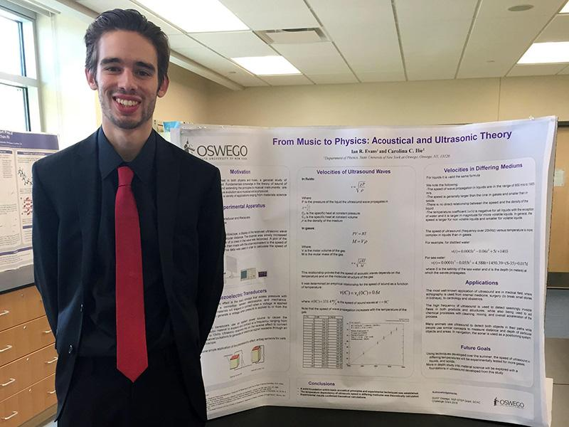 Physics student Ian Evans presenting research poster